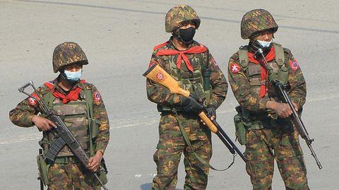 Drei Soldaten in Tarnfleck beobachten mit Gewehren im Anschlag eine Demonstration in Kale, Myanmar
