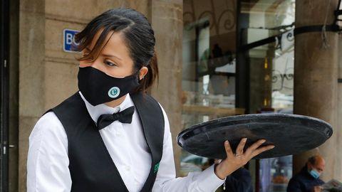 Eine Kellnerin mit langen schwarzen Haaren und klassischem schwarz-weißem Outfit trägt mit links ein rundes Tablett
