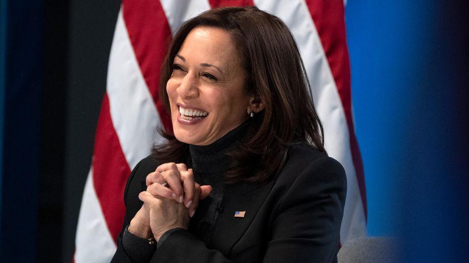 Kamala Harris lächelnd vor US Flagge