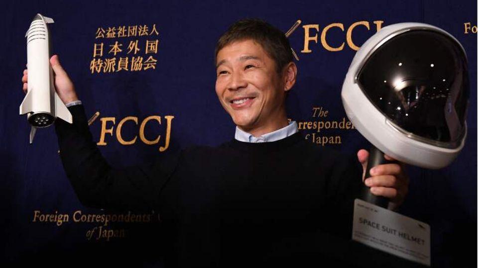 Der MilliardärYusaku Maezawa vor einer schwarzen Wand, er hält eine Modellrakete und einen Raumfahrthelm