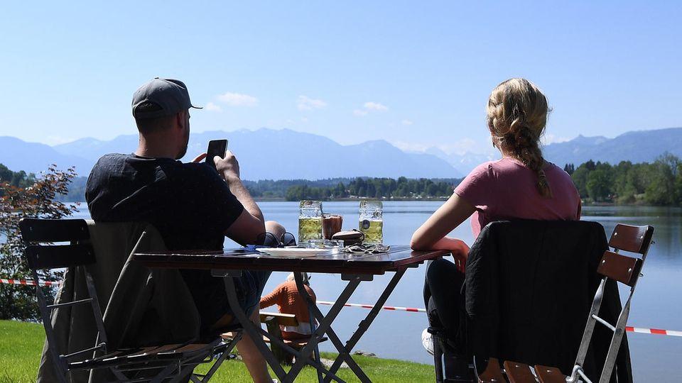 An einem Tisch sitzen ein Mann und eine Frau im Freien, haben je ein Bier vor sich und blicken bei Sonne über einen See