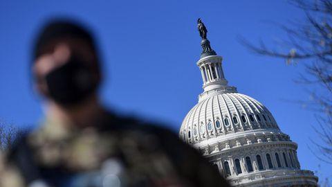 Ein Mitglied der Nationalgarde steht in Uniform und Schutzweste vor der Kuppel des Kapitols in Washington