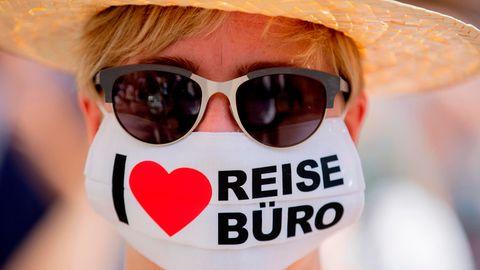 """Eine Frau mit Sonnenbrille trägt eine Maske mit der Aufschrift """"I love Reisebüro"""""""