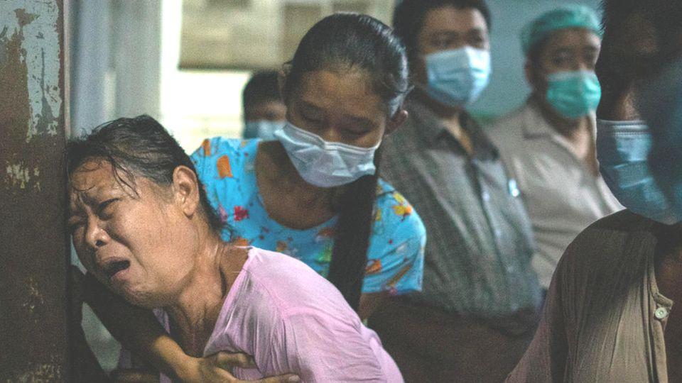 In schwachem Licht lehnt eine mittelalte Asiatin mit von Trauer gezeichnetem Gesicht am Eingangstor eines Krankenhauses