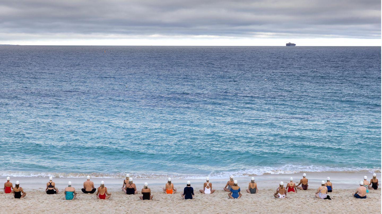 """Bild 1 von 7der Fotostrecke zum Klicken:Mit Blick auf den Horizont sitzen die Teilnehmer der """"lebendigeKunstinstallation"""" am Meer."""