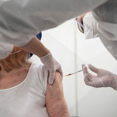 Eine Krankenschwester impft im Impfzentrum in der Paul-Horn-Arena eine 92-jährige Frau mit Covid-19 Impfstoff