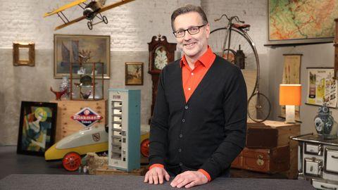 Detlev Kümmel steht im Bares für Rares Studio in Pulheim und lächelt in die Kamera
