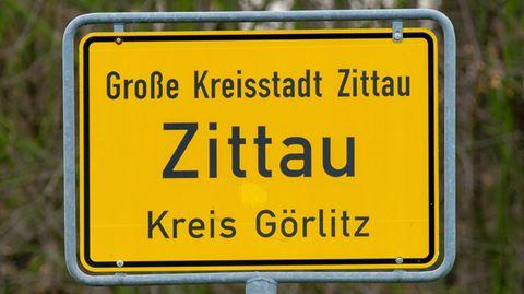 """Auf einem gelben Ortsschild steht """"Große Kreisstadt Zittau. Kreis Görlitz"""""""