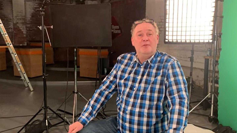 Walter Lehnertz sitzt im Studio von Bares für Rares in Pulheim in Köln. Im Hintergrund ist der Händlerraum zu sehen.