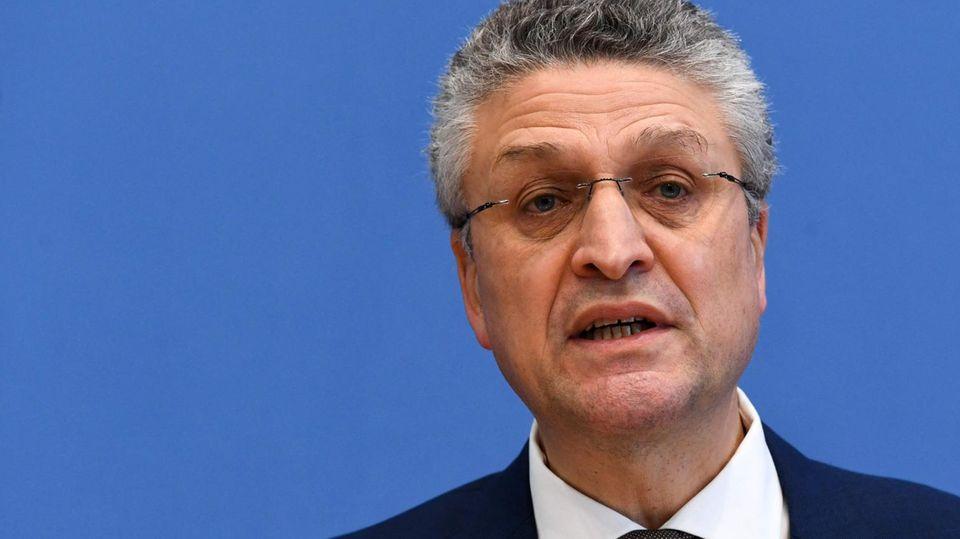 Ein weißer Mann in Anzug und Krawatte sitzt vor einer blauen Wand und spricht. Er hat grauweiße Locken und eine randlose Brille