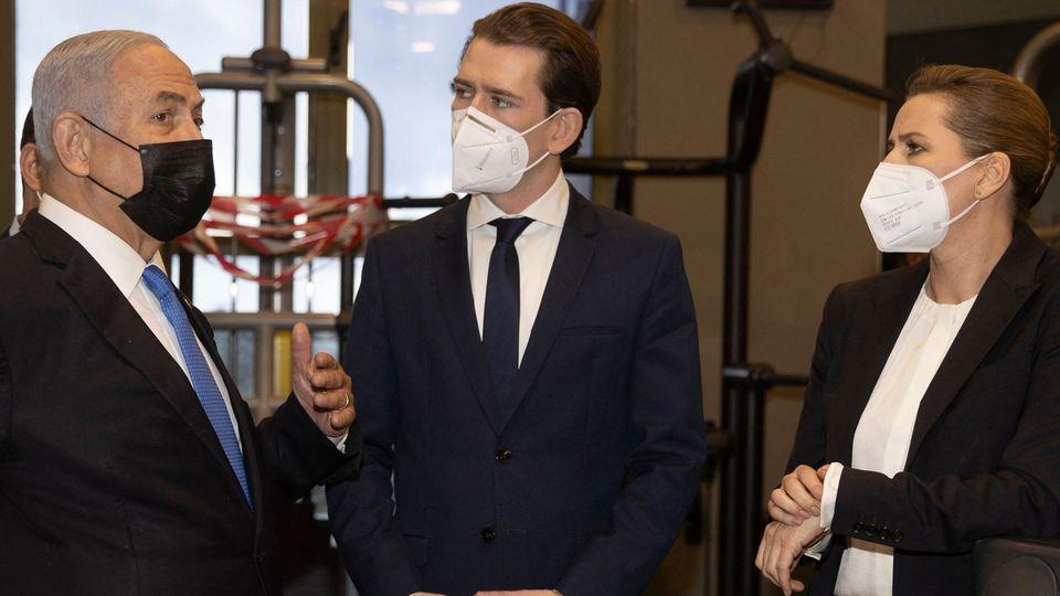 Links steht ein grauhaariger älterer Mann im Anzug,