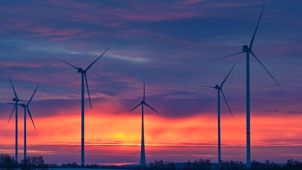 Windkraftanlage in Schleswig-Holstein vor einem Sonnenuntergang.