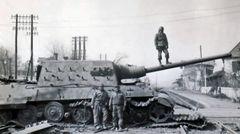 Alliierte Soldaten neben einem liegengebliebenen Jagdtiger.