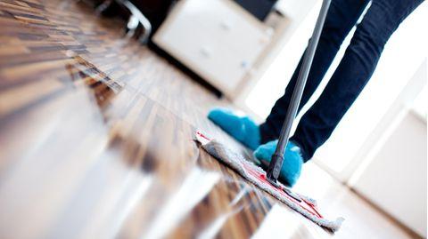 Parkett reinigen: Frau pflegt Holzboden mit einem Wischmopp