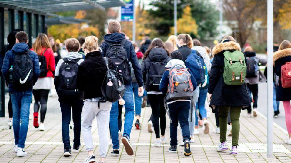 Schülerinnen und Schüler gehen mit ihren Schulrucksäcken von einer Bushaltestelle zu ihrer Schule