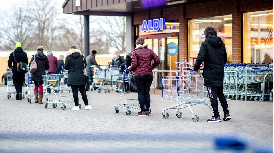 Zahlreiche Kunden warten auf die Öffnung einer Filiale von Aldi im Stadtteil Bult