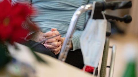 Eine Bewohnerin in einem Alten- und Pflegeheim hat die Hände zum Gebet gefaltet