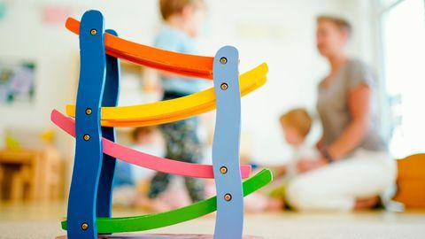 Eine Erzieherin spielt in einer Kindertagesstätte hinter einer Rollbahn mit Kindern
