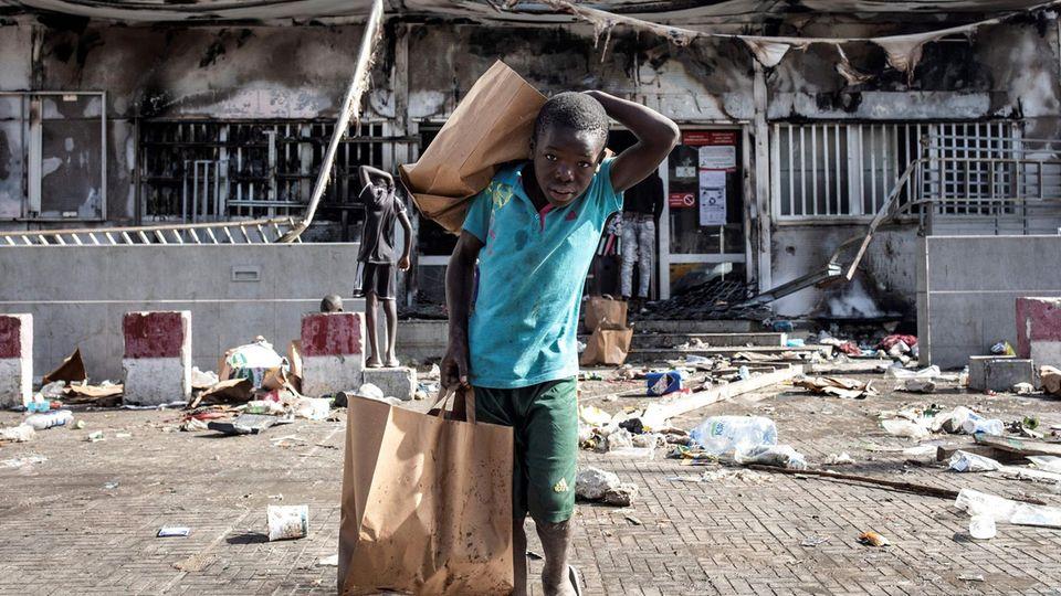 Ein Junge kommt mit Tüten voller Lebensmittel aus einem geplündertem und niedergebranntem Supermarkt.