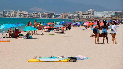 Menschen sonnen sich und schwimmen am Strand von Arenal auf Mallorca