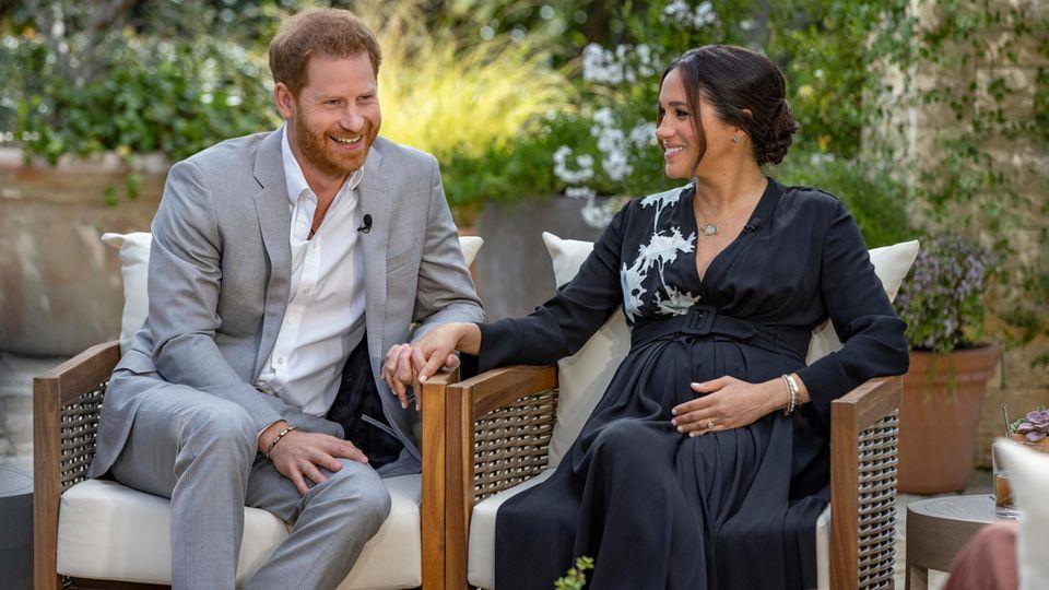 Harry und Meghan sitzen im Garten und schauen Oprah Winfrey an