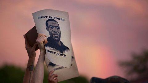 Demonstranten halten während eines Protestes Zettel mit dem Porträt von George Floyd