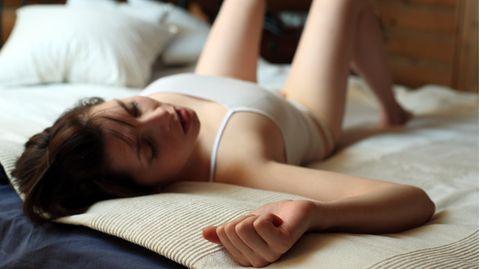 Frau liegt leicht bekleidet auf einem Bett.