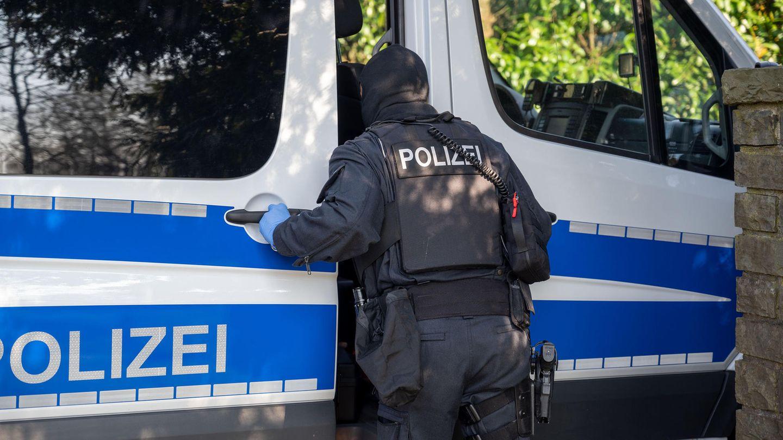 Nordrhein-Westfalen:Ein Polizist steht imRahmen einer Razzia an einem Polizeifahrzeug