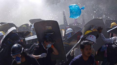 Menschen werden während eines Protests gegen den Putsch der Militärjunta auf einer Straße von der Polizei mit Tränengas auseinander getrieben