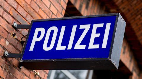 Ein blaues Polizeischild vor einer roten Ziegelwand