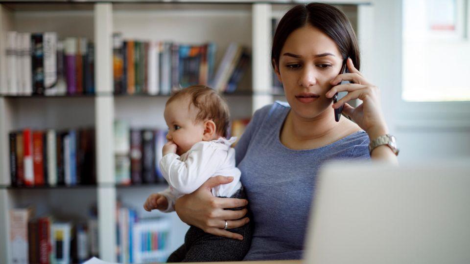 Junge Mutter arbeitet mit Baby