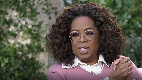 Oprah Winfrey sitzt beim Interview mit Meghan Markle in einem Stuhl und legt die Hände ineinander
