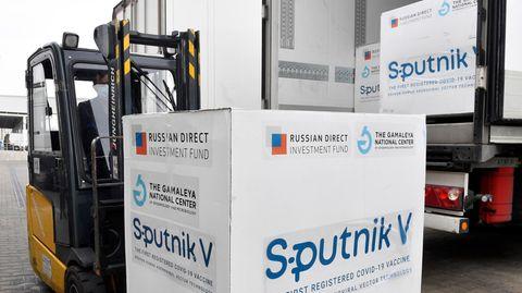 """Ein Gabelstapler lädt einen großen weißen Karton mit blauem """"Sputnik V""""-Schriftzug aus einem Lkw-Auflieger"""