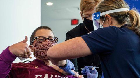 Eine Frau zeigt Damen hoch während sie in Connecticut gegen Corona geimpft wird