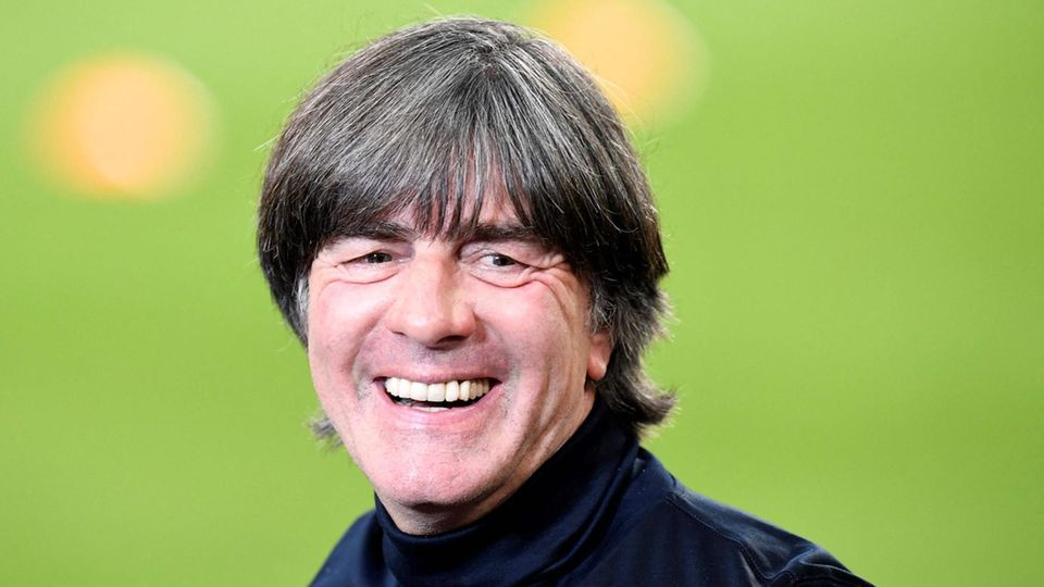 In a dark blue turtleneck Sweater Jogi Löw is on the edge of a football space with a laugh. The grass in the Background is out of focus