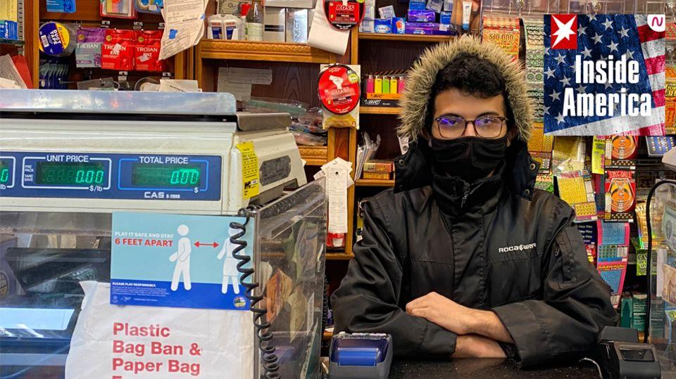 Ein dunkelhaariger junger Mann sitzt in schwarzer Winterjacke und mit verschränkten Armen hinter dem Tresen eines kleinen Ladens