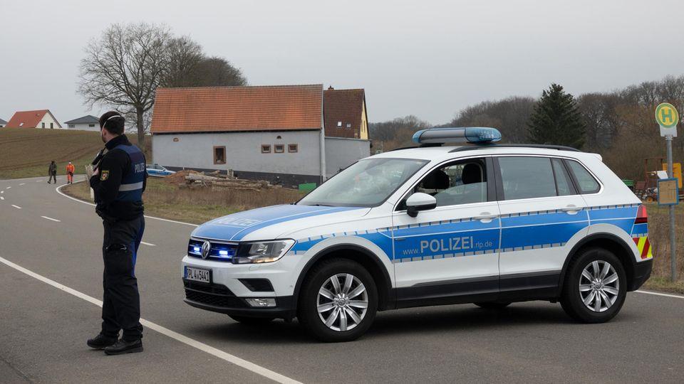 Ein Polizist sperrt mit einem Einsatzfahrzeug der Polizei eine Straße