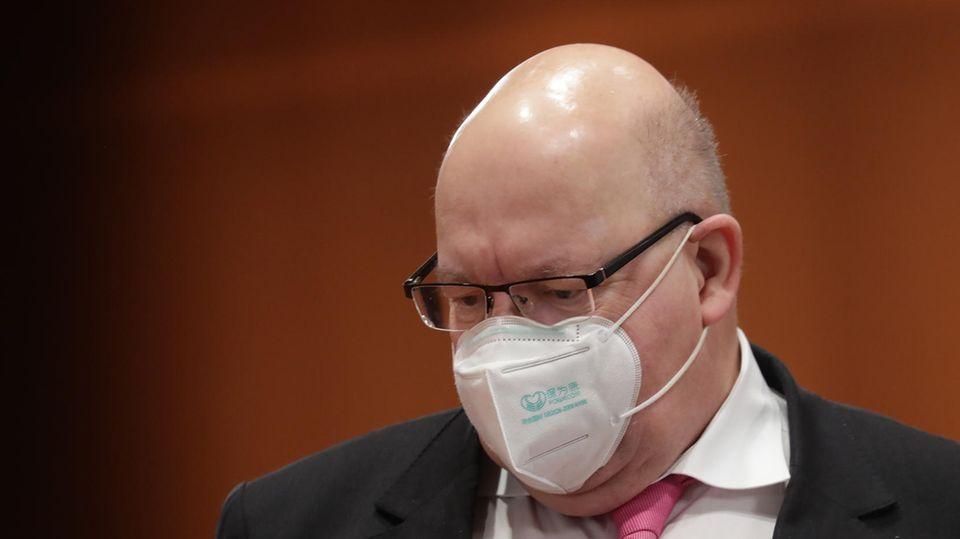 Ein korpulenter Mann mit Halbglatze trägt Brille, FFP2-Maske und einen schwarzen Anzug mit einer rosa Krawatte
