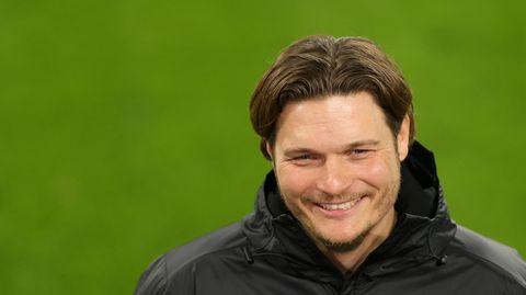 Ein Mann mit dunkelblondem Seitenscheitel grinst, während er auf einem Fußballplatz interviewt wird