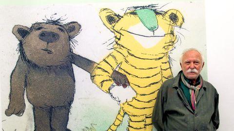 Autor und Illustrator Janosch steht vor seiner Zeichnung bei einer Ausstellung.