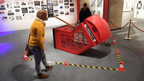 Leicht gebeugt betrachtet eine junge Frau in senfgelbem Wollpulli eine am Boden liegende, geknickte rote Telefonzelle von Banksy