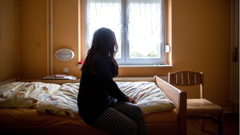 Eine Frau sitzt in einem Frauenhaus auf einem Bett und schaut zum Fenster