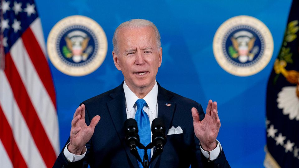 """Joe Biden steht am Pult mit dem Wappen des US-Präsidenten. Hinter ihm eine blaue Wand mit weißem """"Covid-19 Response""""-Schriftzug"""