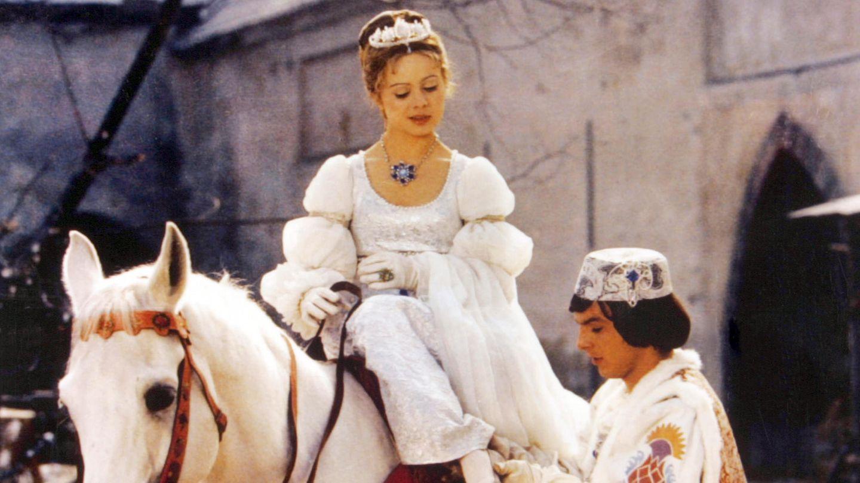 Aschenbrödel sitzt auf einem Pferd, Prinz probiert, ob ihr der Schuh passt