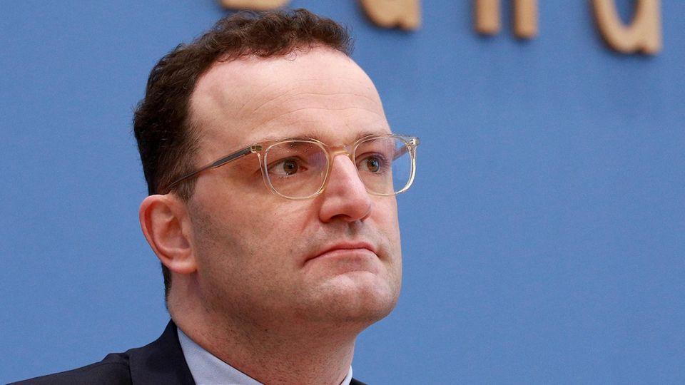 Ein Mann mit braunen Locken und durchsichtigem Brillengestell sitzt im Anzug vor einer blauen Wand