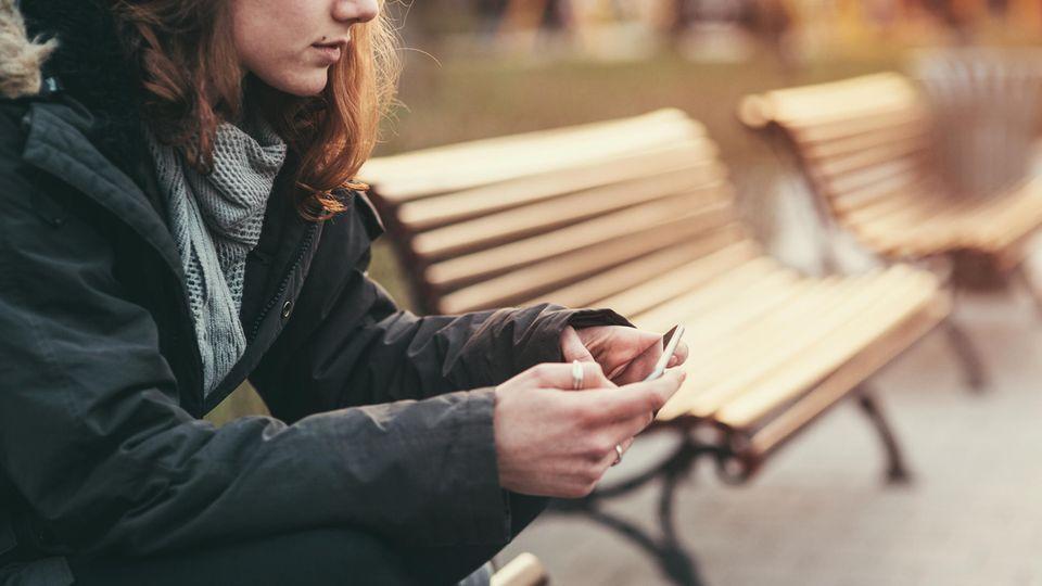 Junge Frau sitzt alleine auf einer Bank und schaut auf ein Smartphone.