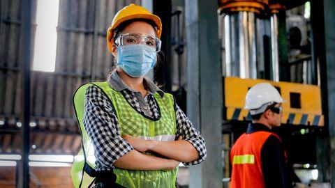 Arbeiterin mit hygienischer Maske steht selbstbewusst in einer Halle - mit ihrem Mitarbeiter als Hintergrund