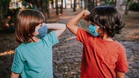 Zwei Kinder mit Masken begrüßen sich mit den Ellbogen