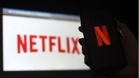 Eine Hand hält ein Smartphone mit dem Netflix-Bildschirm vor einem Laptop, auf dem ebenfalls ein Netflix-Logo zu sehen ist