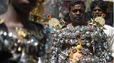Chennai, Indien. DasMahashivaratriist einer der wichtigsten Feiertage im Hinduismus, zu Ehren des Gottes Shiva. Dieser Mann nimmt an der religiösen Prozession teil, reich am Körper geschmückt mitPaaladais, Gefäßen zur Fütterung von Säuglingen.